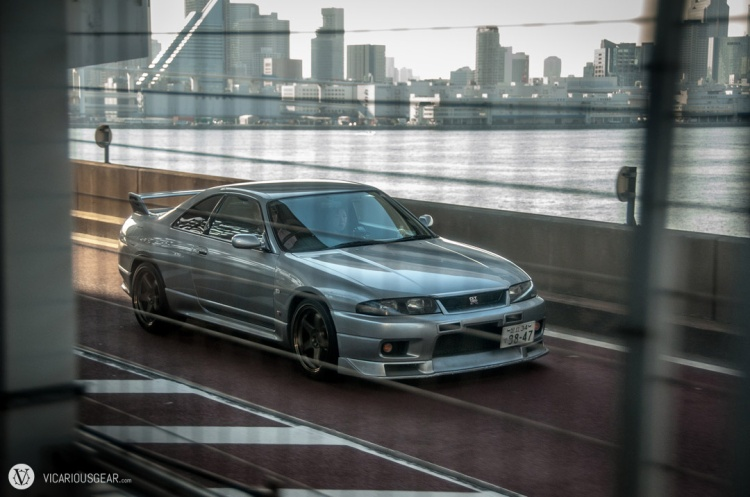 A clean Skyline R33 with lip and Nismo rims crossing the rainbow bridge in Tokyo.