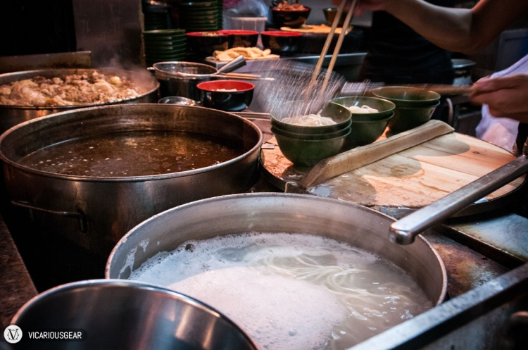 Huge stock pots with (from front to back) noodles, broth and possibly the signature hot sauce being made.